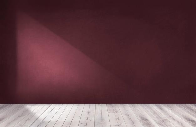 Parede vermelha de borgonha em um quarto vazio com um piso de madeira
