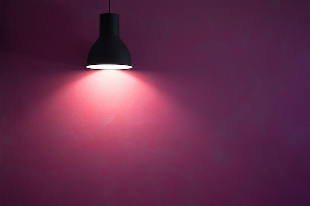 Parede vermelha iluminada pela lâmpada de cone elegante preto vintage.