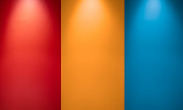 Parede vermelha, laranja ou amarela e azul vazia com holofotes