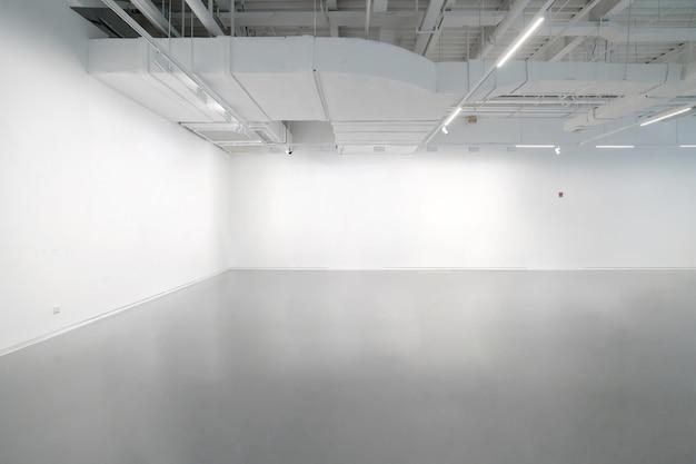 Paredes brancas e pisos de cimento cinza no espaço interior
