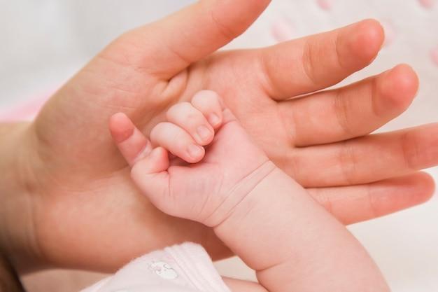 Parental mão segura o bebê