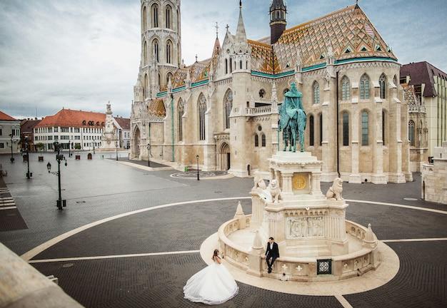 Pares à moda bonitos novos de recém-casados que andam pelo bastião do pescador em budapest, hungria. vista do topo