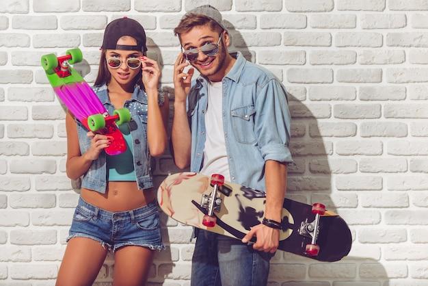 Pares adolescentes à moda na roupa de brim.
