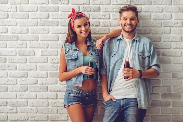 Pares adolescentes à moda que guardam a garrafa da água de soda.