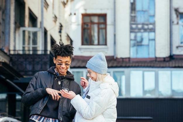 Pares adolescentes inter-raciais à moda que fazem o divertimento olhando no telefone móvel