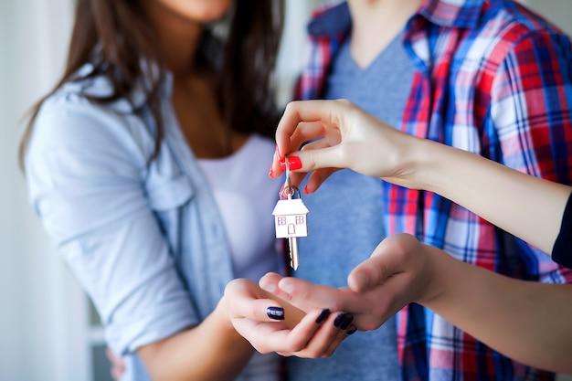 Pares adultos novos dentro da sala com as caixas que guardam a bandeira nova das chaves da casa.
