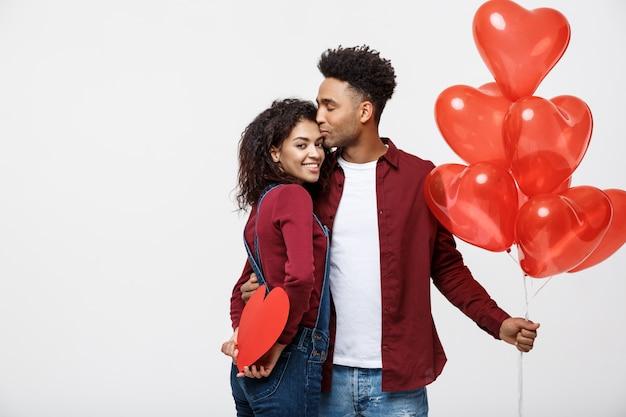 Pares afro-americanos attactive novos que guardam o balão e o papel do coração.