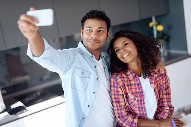 Pares afro-americanos que fazem o selfie na cozinha.