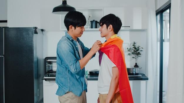 Pares alegres asiáticos que estão e que abraçam a sala em casa. jovens bonitos lgbtq + homens beijando feliz relaxar resto juntos passam tempo romântico na cozinha moderna com bandeira de arco-íris em casa de manhã.