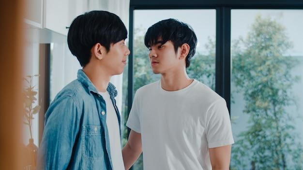Pares alegres asiáticos que estão e que abraçam a sala em casa. jovens bonitos lgbtq + homens beijando feliz relaxar resto juntos passam tempo romântico na cozinha moderna em casa de manhã.
