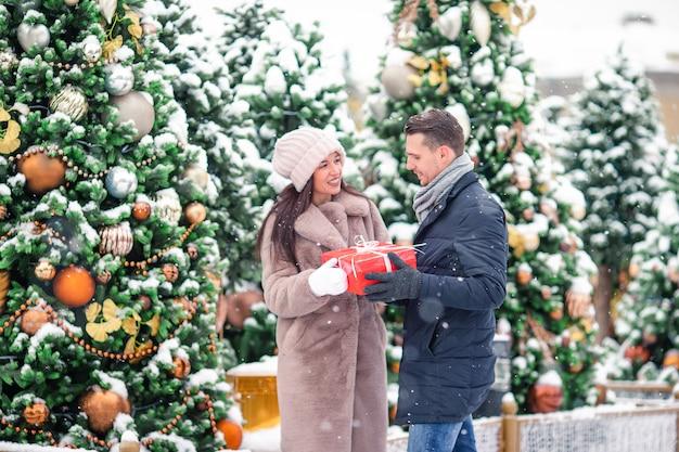 Pares alegres bonitos novos que comemoram o natal na rua da cidade e que dão o presente entre si.