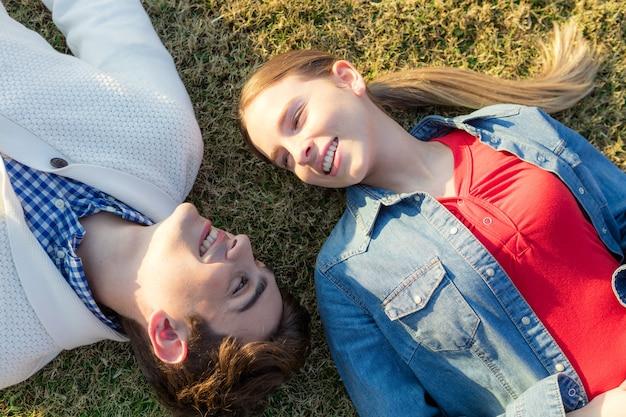 Pares alegres deitada na grama e olhando para o outro