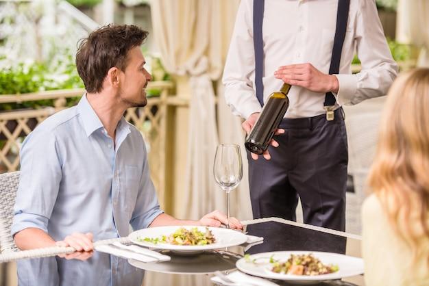 Pares alegres em um restaurante que pede o vinho.