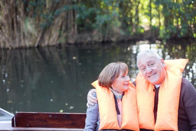 Pares aposentados que têm o divertimento em um barco