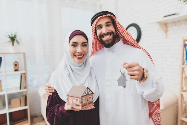 Pares árabes felizes com casa do sonho das chaves da casa.