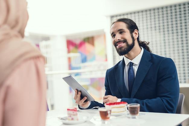 Pares árabes novos que sentam-se no café após a compra. Foto Premium