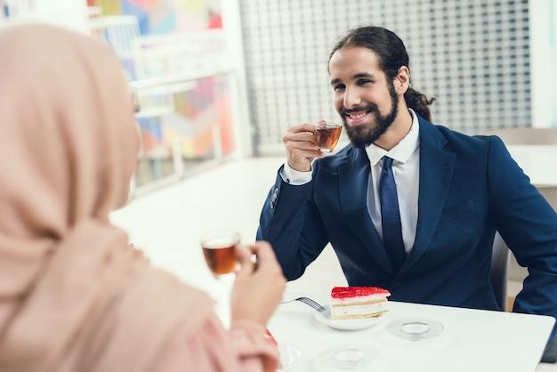 Pares árabes que sentam-se no café após a compra.