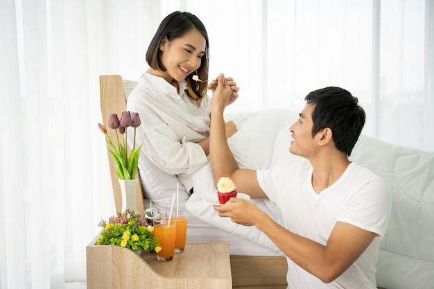 Pares asiáticos que comem um bolo e suco de laranja no quarto, conceito de pares bonitos.