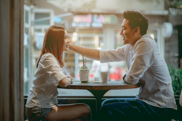 Pares asiáticos que falam felizmente no café durante o dia.