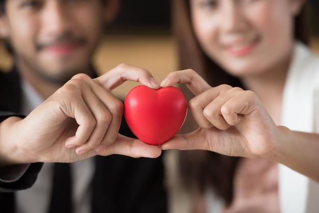 Pares asiáticos que guardam o sinal do coração com feliz.