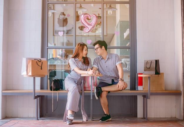 Pares asiáticos que sentam-se e que falam felizmente após a compra.