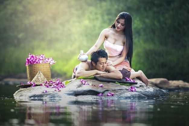 Pares asiáticos que têm o conceito do tratamento da beleza do salão de beleza da massagem e dos termas. ela está muito feliz