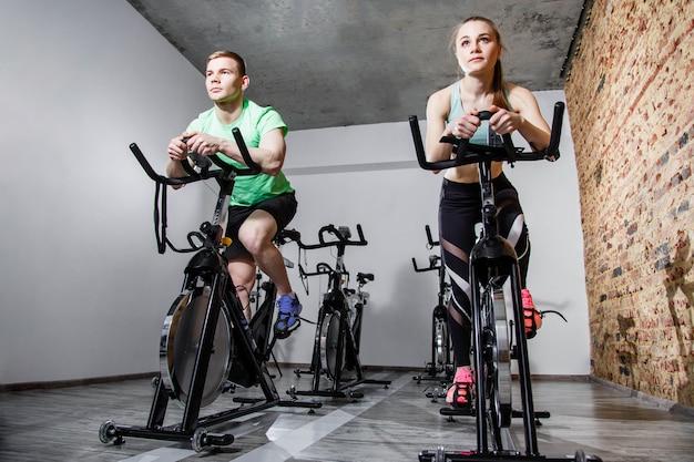 Pares ativos felizes que exercitam com bicicletas em um gym. vista frontal