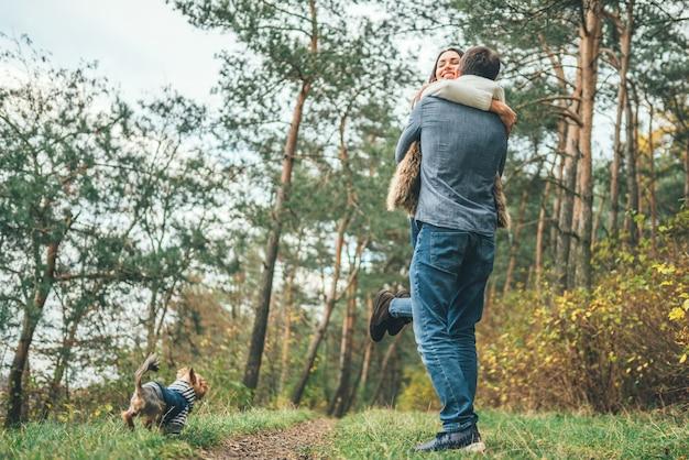 Pares bonitos com o yorkshire terrier pequeno que anda na floresta.