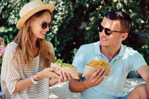 Pares bonitos felizes que comem o cachorro quente, passando o tempo com prazer, ao ar livre. horário de verão.