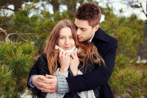 Pares consideravelmente abraçando e flerta em um dia de inverno