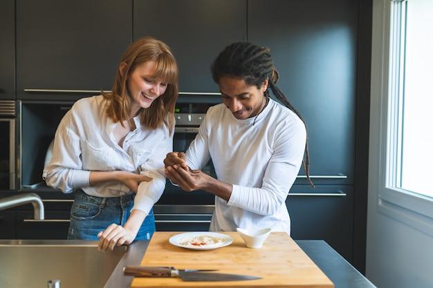 Pares da raça misturada que cozinham junto na cozinha.