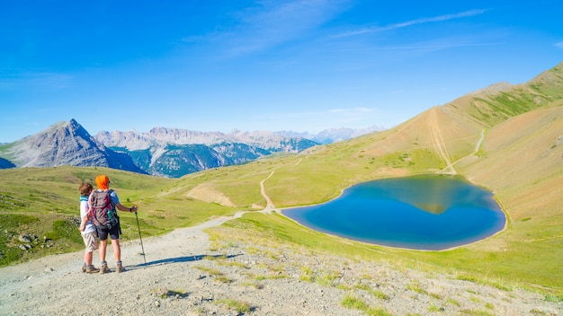 Pares de caminhante na parte superior da montanha que olha picos azuis do lago e de montanha.