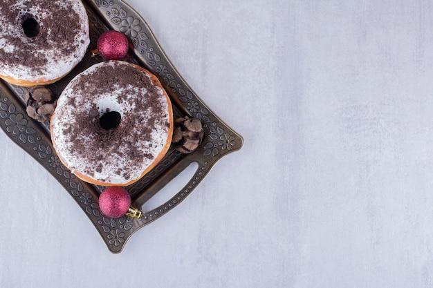 Pares de cones de cipreste, donuts e decorações de natal em uma bandeja no fundo branco.