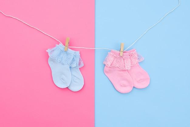 Pares de meias de bebê fofas azuis e rosa penduradas no varal