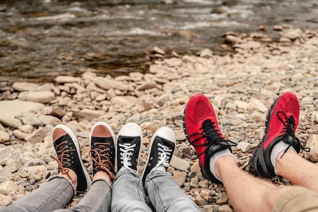 Pares de pernas de árvores em sapatos desportivos pretos apoiados em pedras ao ar livre