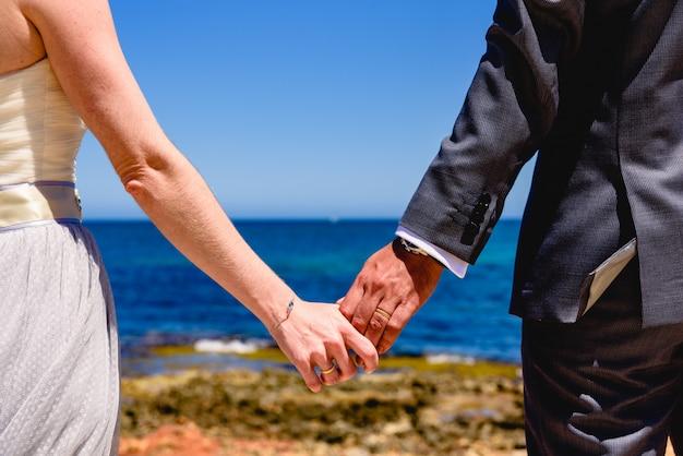 Pares de recém-casados no amor com suas mãos das posses das costas que olham o mar.