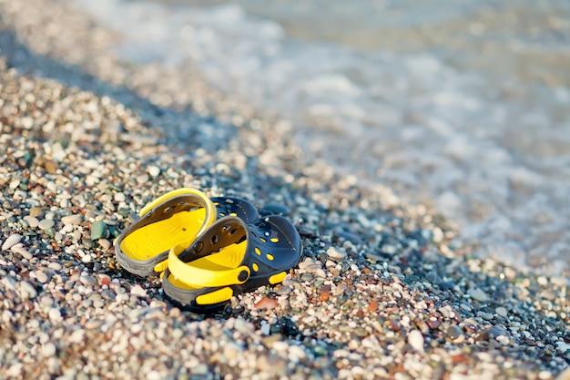 Pares de sandálias da criança de um nadador em uma praia no verão.