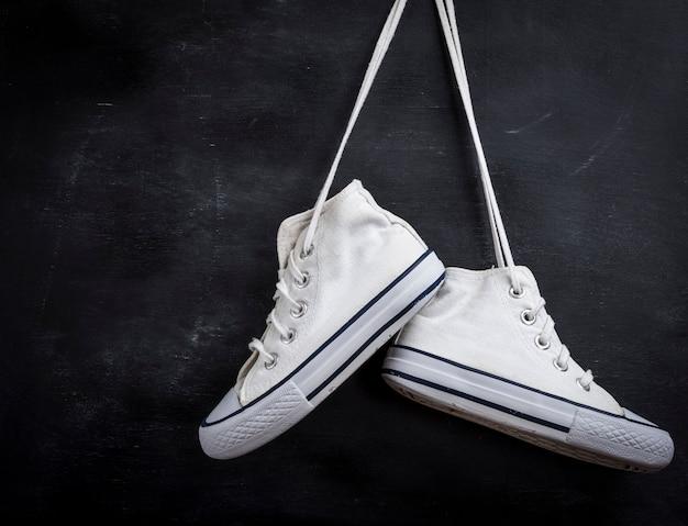 Pares de sapatos têxteis usados pendurar em preto