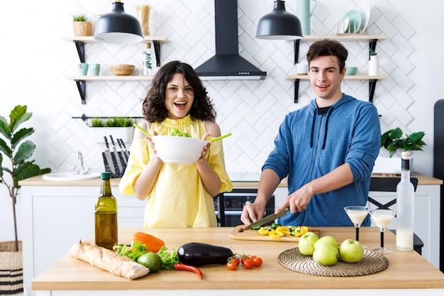 Pares de sorriso bonitos novos que cozinham junto na cozinha em casa. jovens estão preparando uma salada em uma boa cozinha