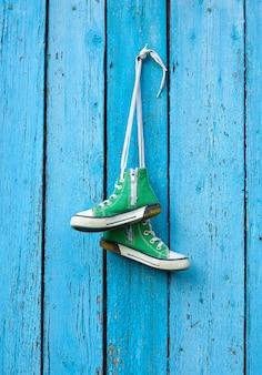 Pares de velhos tênis clássicos de têxteis verdes penduram em uma corda