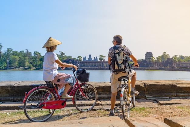 Pares do turista que dão um ciclo no templo de angkor, camboja. fachada principal de angkor wat