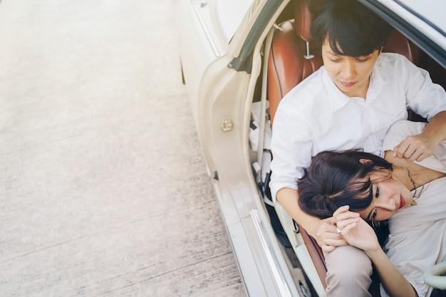 Pares doces do retrato que amam no carro clássico na viagem por estrada. amor, dia dos namorados e conceito de casamento.