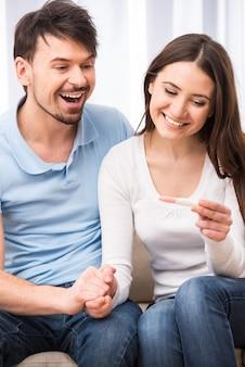 Pares enamoured felizes com teste de gravidez.