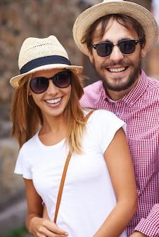 Pares encantadores com chapéus e óculos de sol