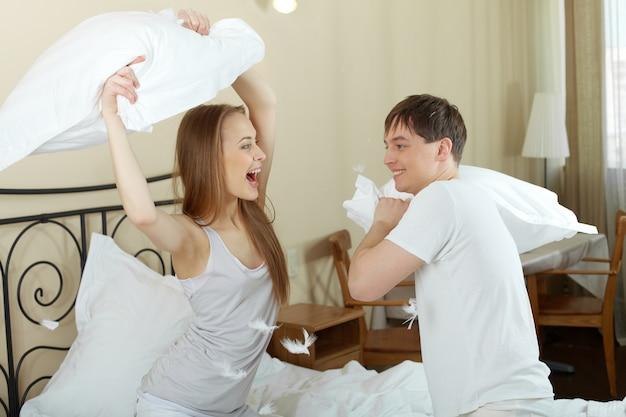 Pares engraçados brigando com travesseiros na cama