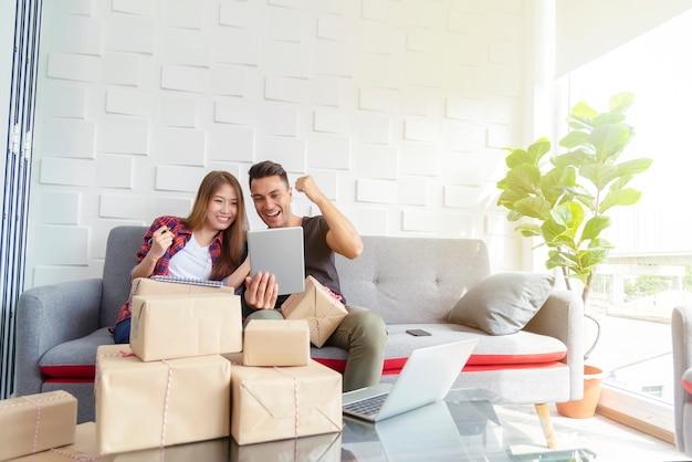 Pares felizes após a venda em linha bem sucedida em casa. empresa de pequeno porte com o conceito de tecnologia.