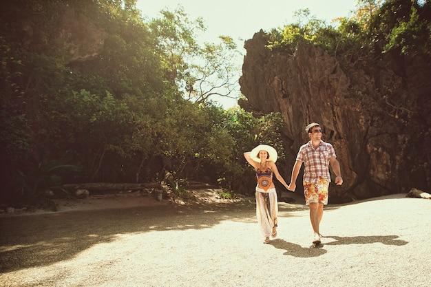Pares felizes bonitos que guardam as mãos, andando na praia com montanhas em um dia ensolarado, fora. uma menina em um chapéu e um cara de férias em um país tropical. viagens de estilo de vida e turismo, lua de mel