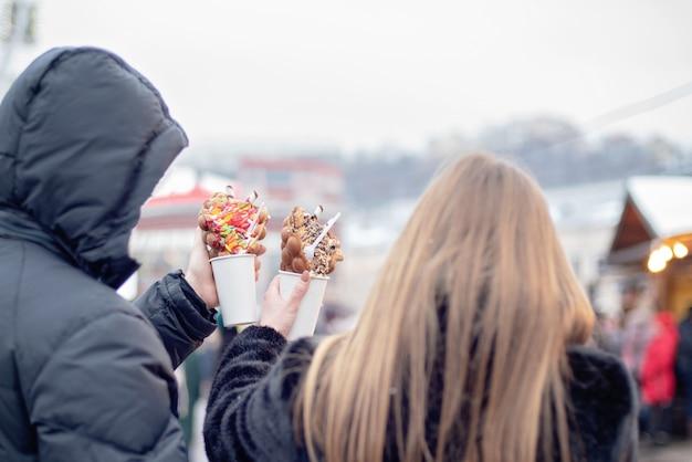 Pares felizes na roupa morna no amor que comem waffles da bolha na feira do natal. feriados, inverno, natal e pessoas