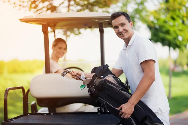 Pares felizes no carro de golfe que leva o equipamento de golfe.