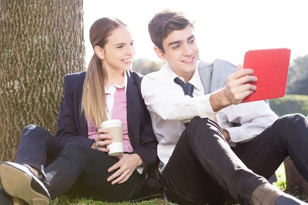 Pares felizes que tomam selfie com o tablet